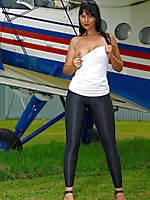 Gorgeous MILF posing in front of a plane | MyBigMILFBooty.com